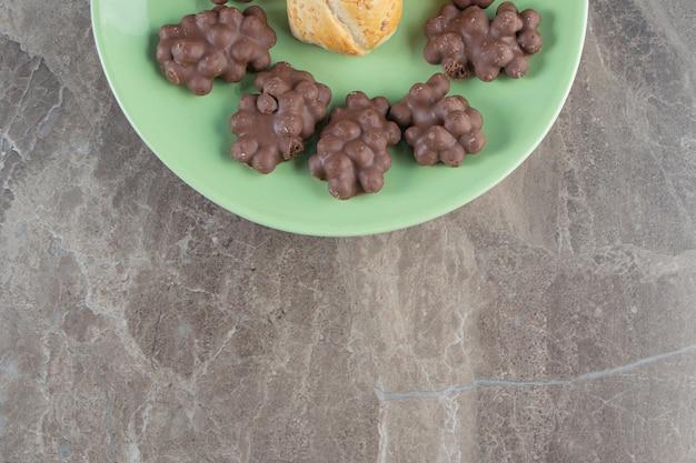 Haselnussschokolade und -plätzchen auf einem teller auf blau.