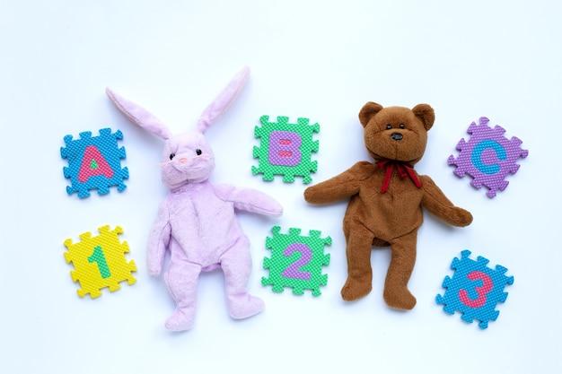 Hasen-spielzeug und teddybär mit englischem alphabet-puzzle und ziffern auf weiß. bildungskonzept, kopierraum
