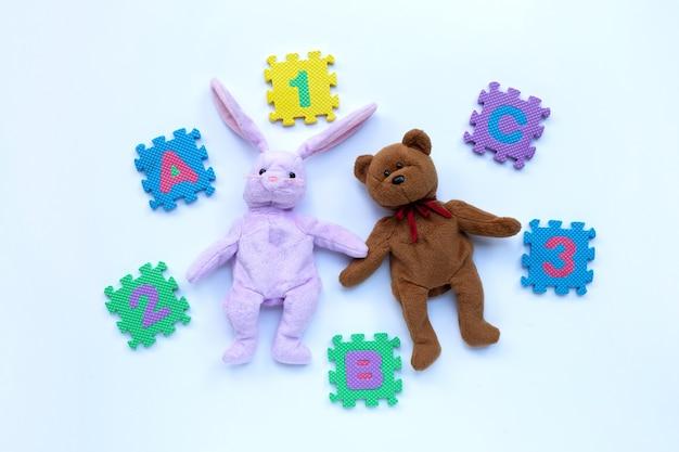 Hasen-spielzeug und teddybär mit englischem alphabet-puzzle und ziffern auf weiß. bildungskonzept
