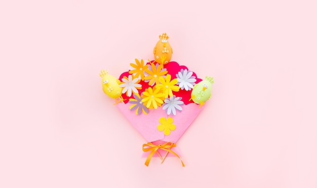 Hasen- und bastelblumen auf rosa hintergrund am ostertag. ostern im frühling feiern. draufsicht.