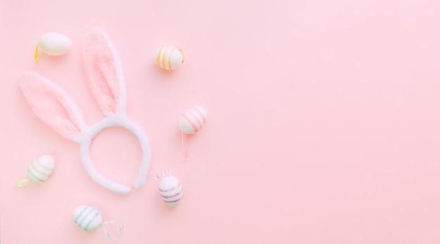 Hasenohren und eier auf rosa hintergrund am ostertag. ostern im frühling feiern. platz für text. banner