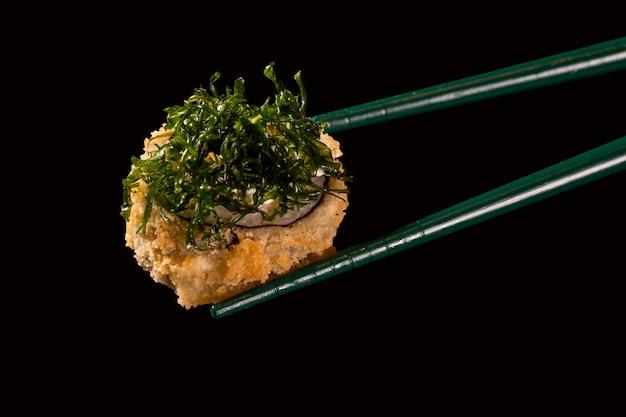 Hashi halten sushi und rollen isoliert über schwarzem hintergrund