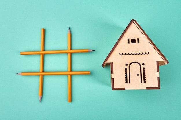 Hashtag aus bleistiften und miniaturholzhaus auf türkisfarbenem tisch