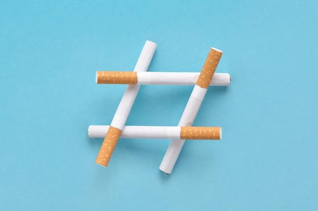 Hashtag-schild aus zigaretten auf blau, symbol für rauchverbot oder keinen tabaktag.
