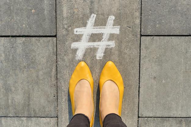Hashtag-symbol auf grauem bürgersteig mit frauenbeinen