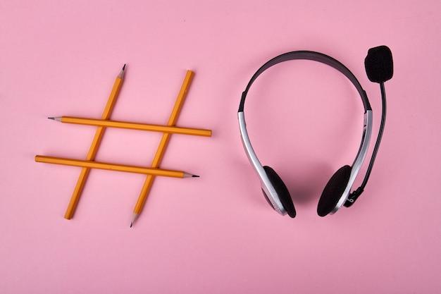 Hashtag-symbol mit gelben stiften und headset auf rosa gemacht