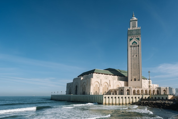 Hassan ii moschee, umgeben von wasser und gebäuden unter blauem himmel und sonnenlicht