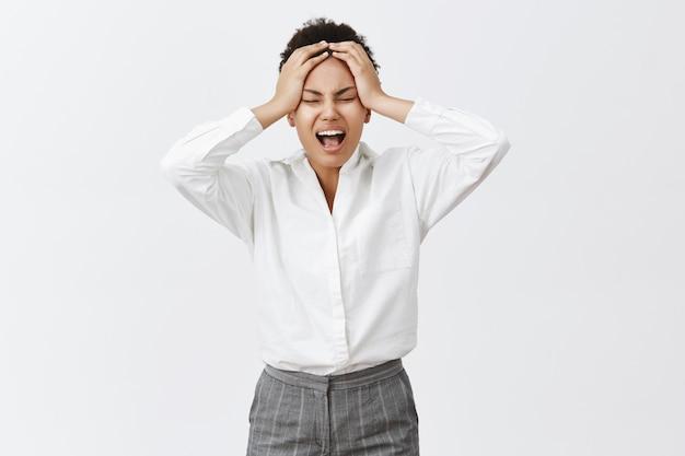 Hasse montage. unglückliche, gestörte und verzweifelte junge, entschlossene geschäftsfrau in formellem outfit, die vor stress und unangenehmen gefühlen in der seele schreit, hände auf dem kopf hält, müde und erschöpft