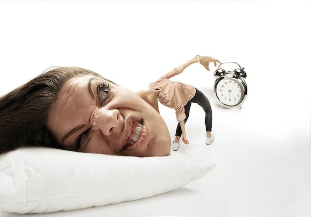 Hassen sie diesen wecker. großer kopf auf kleinem körper, der auf dem kissen liegt. frau kann nicht aufwachen, weil sie kopfschmerzen hat, wütend und verschlafen. konzept des geschäfts, arbeiten, beeilen, fristen.