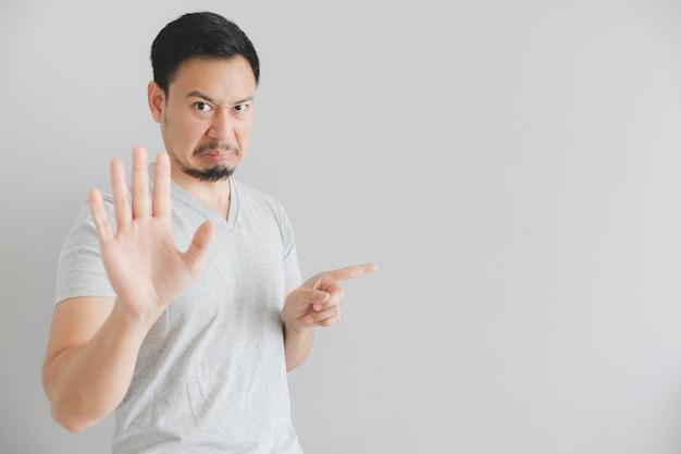 Hassen sie gesicht des mannes im grauen t-shirt mit handpunkt auf leerem raum.