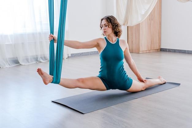 Hatha aero fly yoga konzept schöne junge trainerin zeigt dehnübungen auf blauer hängematte
