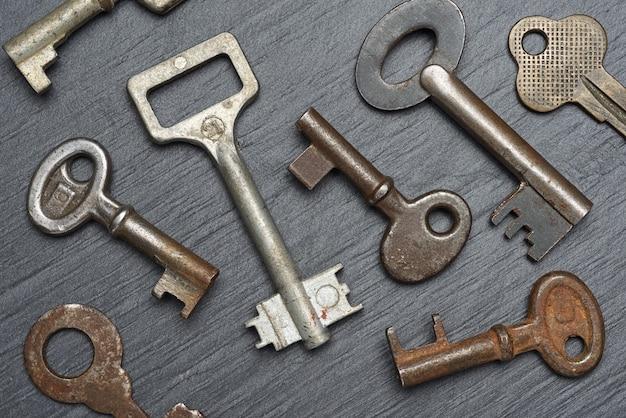 Haufen alter rostiger hebelzuhaltungsschlüssel auf schwarzem schiefer