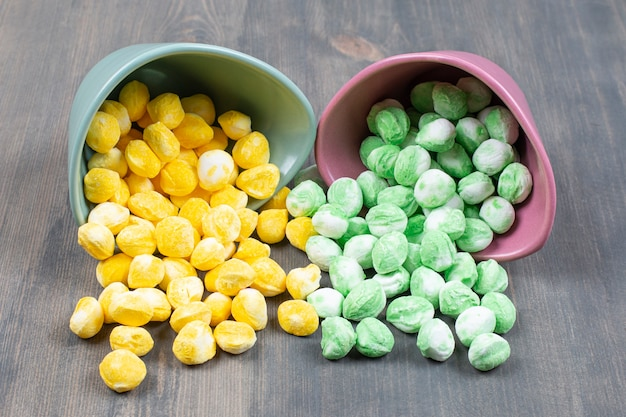 Haufen bunter bonbons aus keramikschalen