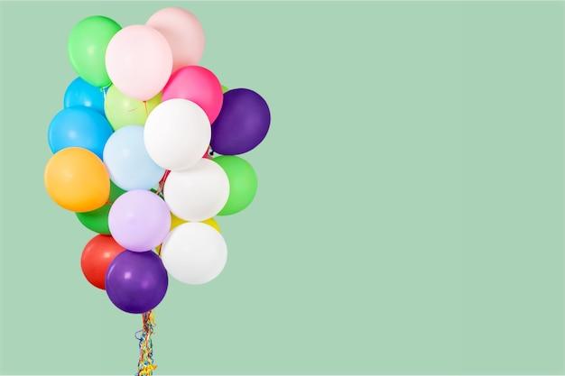 Haufen bunter luftballons auf pastellfarbenem hintergrund