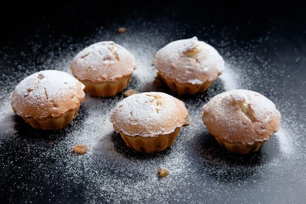 Haufen cupcakes mit zuckerpulver und rosinen auf schwarzem tisch