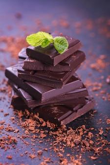 Haufen der dunklen schokolade mit tadellosen blättern auf dunklem hintergrund.