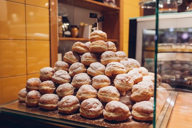 Haufen donuts auf café-vitrine. stapel von desserts mit zuckerpulver