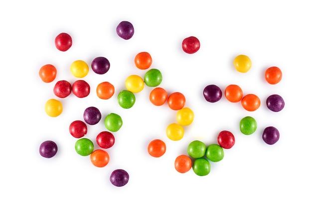 Haufen farbiger runder dragee-süßigkeiten lokalisiert auf weiß, draufsicht, flache lage. mehrfarbige süßigkeiten
