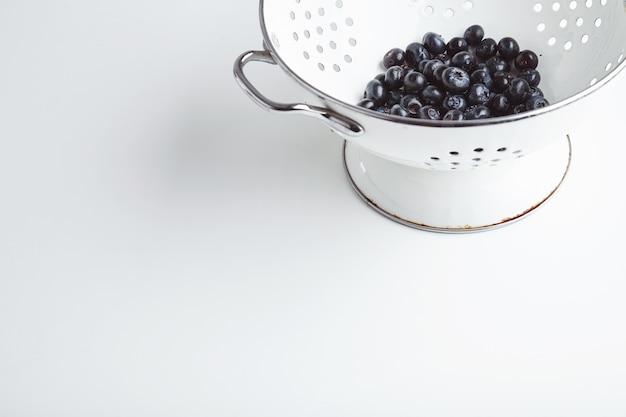Haufen frischer blaubeeren in altem emailfleck, gewaschen und essfertig. leckeres super essen, ideal für ein leichtes frühstück. auf weißem tisch isoliert.