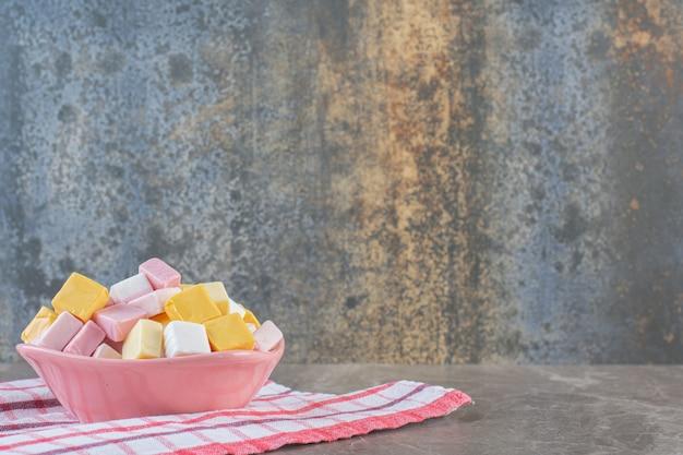 Haufen frischer bonbons in kubischer form in rosa schüssel.