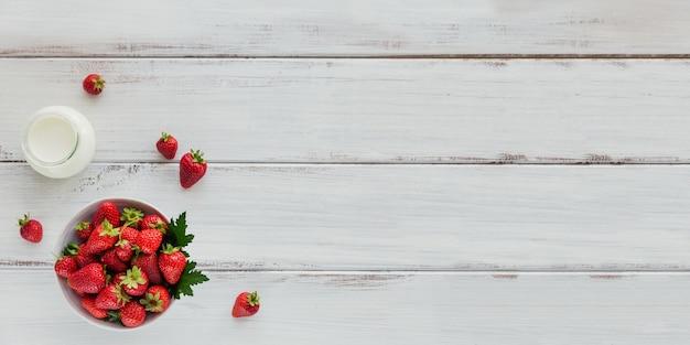 Haufen frischer erdbeeren in der keramikschale auf weißer oberfläche.