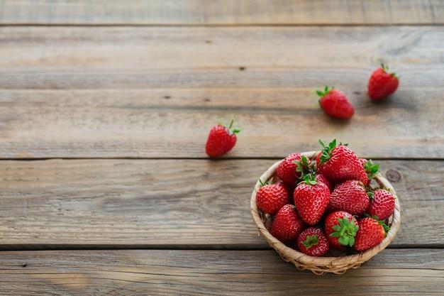 Haufen frischer erdbeeren in einem korb auf rustikaler holzoberfläche. gesundes essen und diätnahrungskonzept.