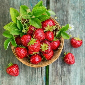 Haufen frischer erdbeeren in einer korbschale auf rustikaler holzoberfläche