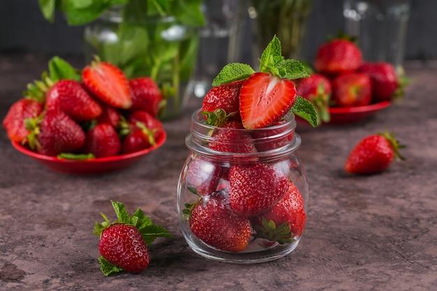 Haufen frischer erdbeeren und minzblätter im glas auf dunkelbrauner oberfläche
