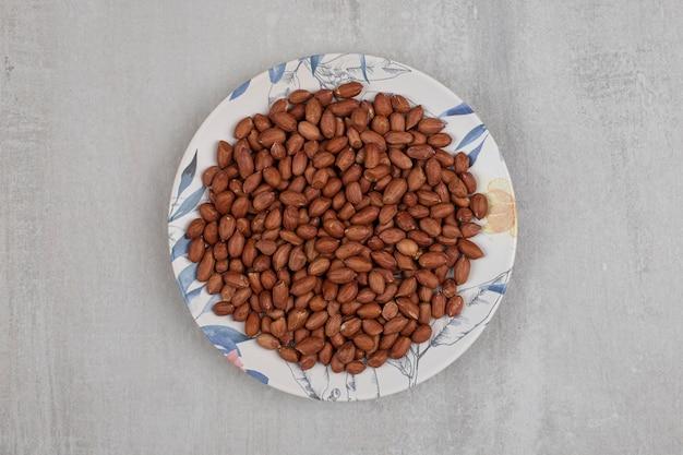 Haufen frischer erdnüsse auf buntem teller.