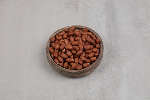 Haufen frischer erdnüsse in holzschale.