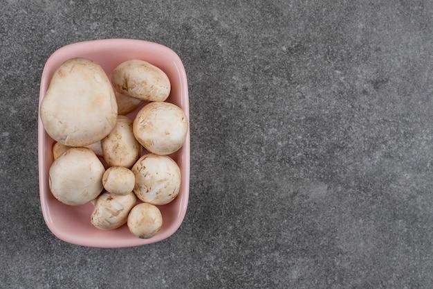 Haufen frischer pilze in rosa schüssel.