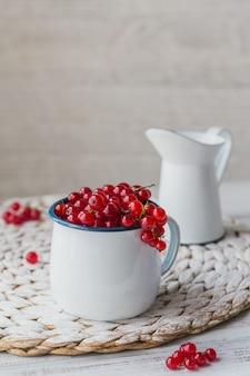 Haufen frischer roter johannisbeere in einem weißen emaille-metallbecher und milch auf weißem holztisch