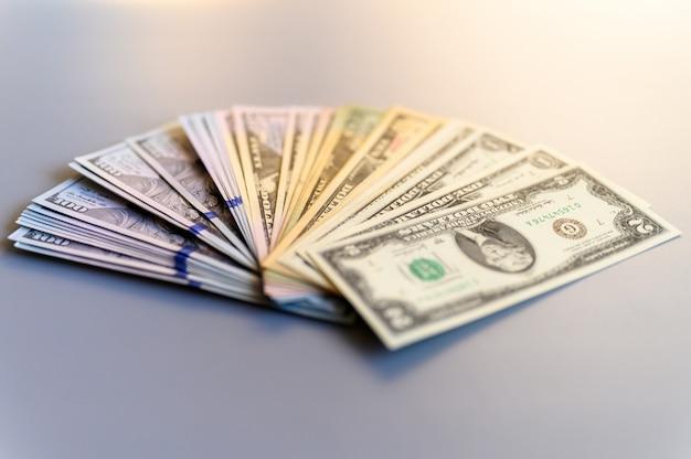 Haufen geld fan auf einem grauen hintergrund. amerikanische dollarnoten verschiedener konfessionen verteilen sich in einem fächer