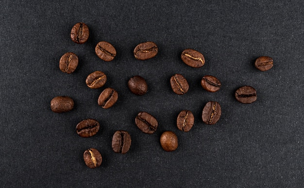 Haufen gerösteter kaffeebohnen auf schwarzem hintergrund