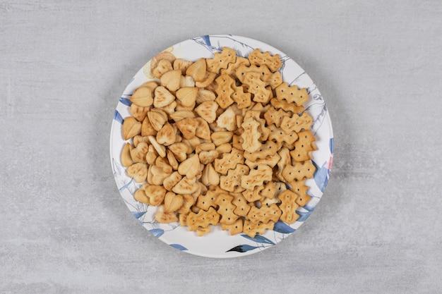 Haufen gesalzener cracker auf buntem teller.