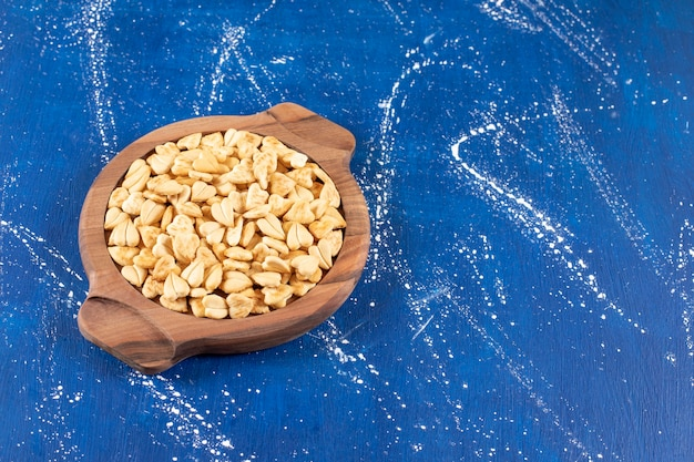 Haufen gesalzener herzförmiger cracker auf holzbrett gelegt
