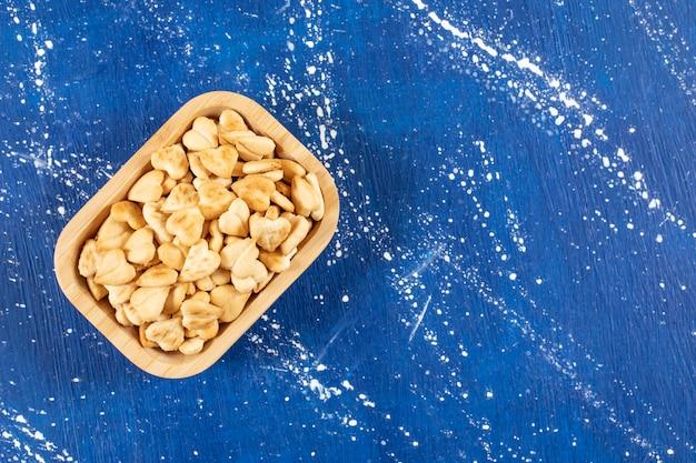 Haufen gesalzener herzförmiger cracker in holzschale gelegt