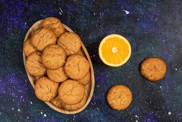 Haufen hausgemachte kekse und halb geschnittene orange über dunklem tisch.