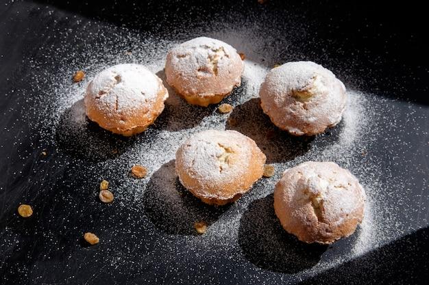 Haufen hausgemachter cupcakes mit zuckerpulver und rosinen auf schwarzem tisch