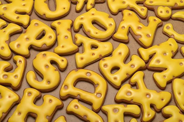 Haufen hausgemachter gelber buchstaben aus lebkuchen-keks-hintergrund.