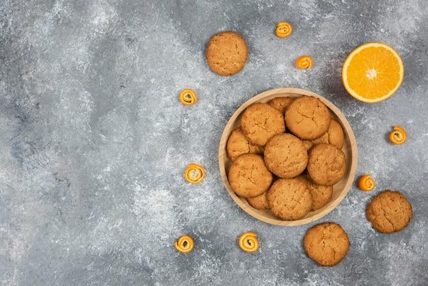 Haufen hausgemachter kekse auf holzbrett und halb geschnittener orange.
