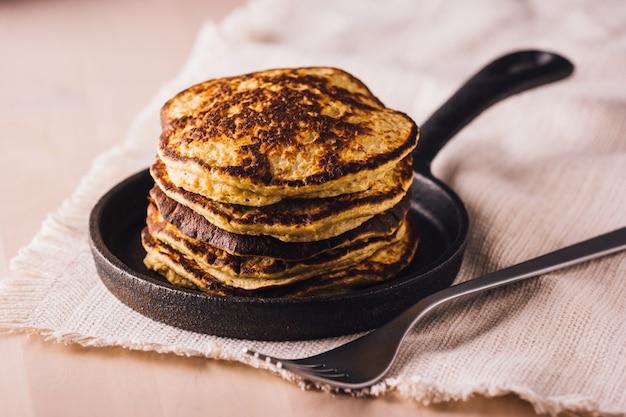 Haufen hausgemachter pfannkuchen frisch zubereitet auf einer kleinen pfanne, essfertig