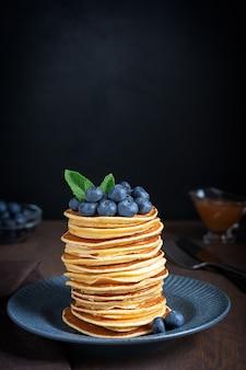 Haufen hausgemachter süßer pfannkuchen mit reifen frischen blaubeeren und grünen minzblättern