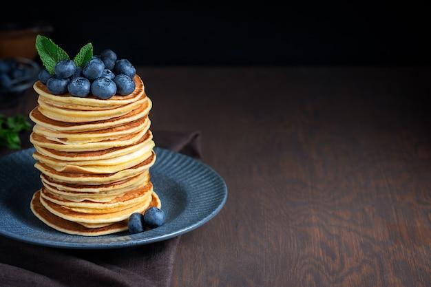 Haufen heißer hausgemachter amerikanischer pfannkuchen, dekoriert mit blaubeeren und minze, serviert auf blaugrauem teller