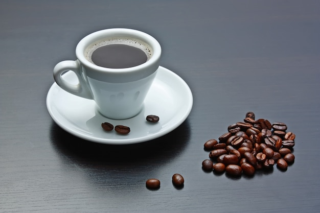 Haufen kaffeebohnen und eine tasse auf einem grauen tisch