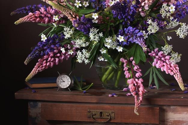 Haufen lupinen. stillleben mit gartenblumen in einer vase und in einem wecker auf dem tisch.