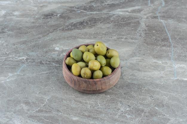 Haufen marinierter oliven in holzschale.