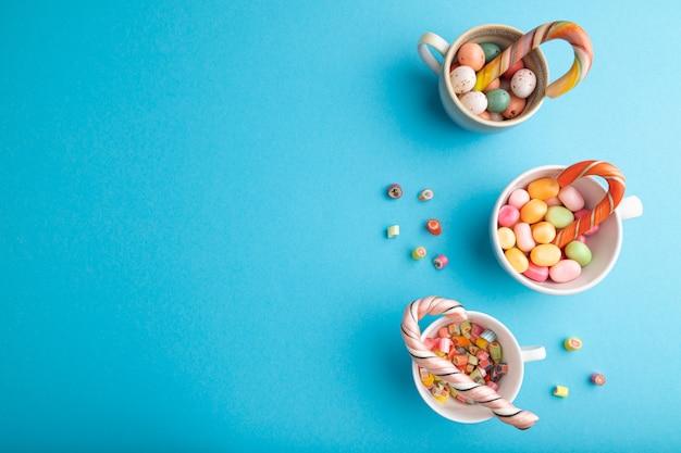 Haufen mehrfarbiger karamellbonbons in tassen auf blauem pastell