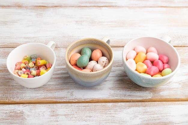 Haufen mehrfarbiger karamellbonbons in tassen auf weißem holz
