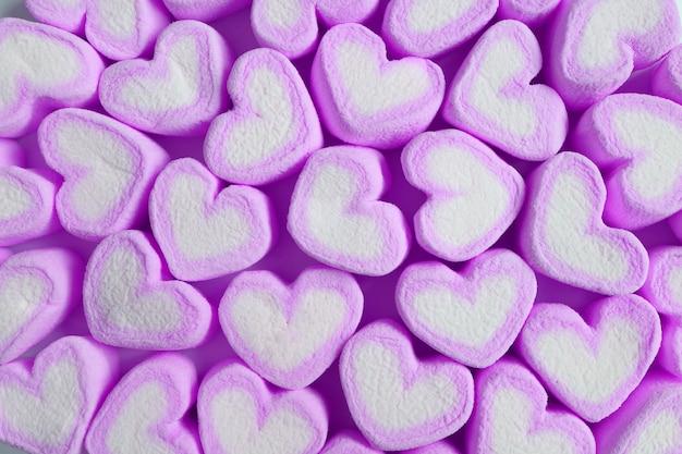 Haufen pastellpurpur und weiße herzförmige marshmallow-bonbons